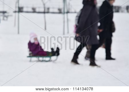 Parents Pull A Sled With Child On The Snow Defocused Winter Background
