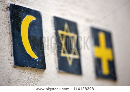 Set of 3 religious symbols: islamic crescent, jewish David's star, christian cross (wall sign on the street of Segovia, Spain)