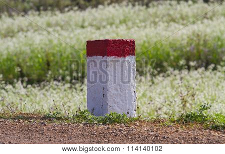 Red and white painted milestone on a country road