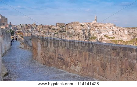 Panoramic View Of Typical Stones And Church Of Matera Shot From Typical Old Street, Under Blu Sky