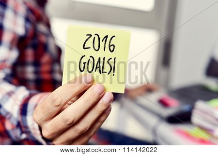 closeup of a young caucasian man wearing a plaid shirt sitting at his desk showing a yellow sticky note with the text 2016 goals written in it