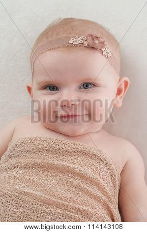 Happy Baby Girl With Beige Flower Headband