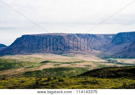 Large Mountain Plateau And Valley Under Cloudy Sky