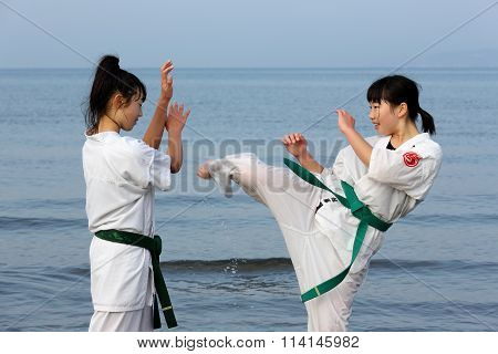Japanese karate girls training at the beach