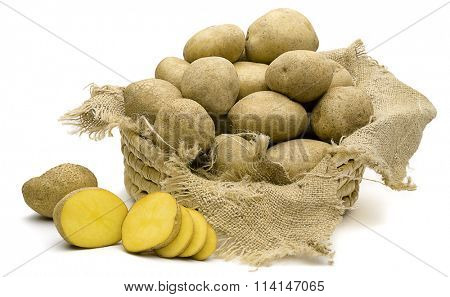 Sliced, unpeeled raw potato in front of old basket isolated on white background.