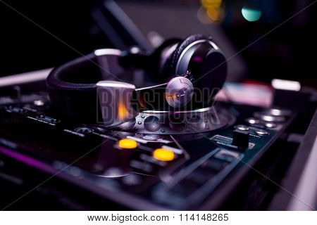 headphones on dj board in night club