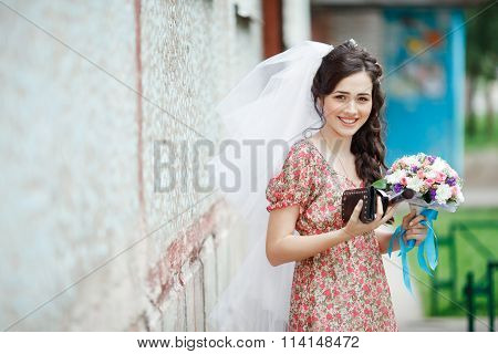 The bride in a simple retro dress with floral pattern, already wearing veil, wedding bouquet and han