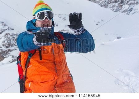 Young man protecting face from snowballs in winter mountains