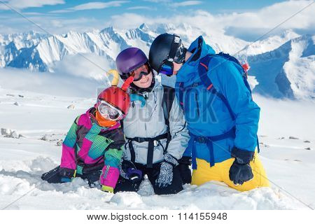 Young family in ski outfit and protective helmets high in the mountains