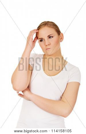 Pensive young woman scratching her head
