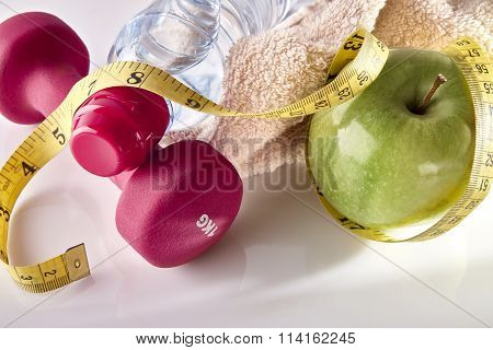 Apple Dumbbells And Tape Measure On White Table Elevated Top