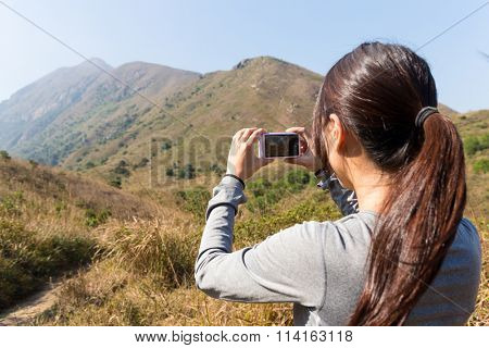 The back view of woman use of the digital camera