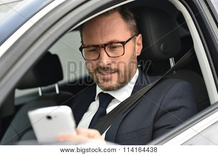 Businessman in car reading message on smartphone