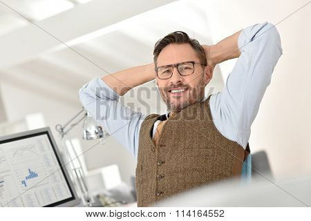 Businessman with eyeglasses relaxing in front of desktop