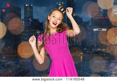happy young woman in crown over night city