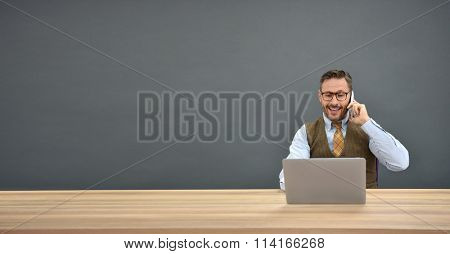 Businessman sitting in front of laptop and talking on phone