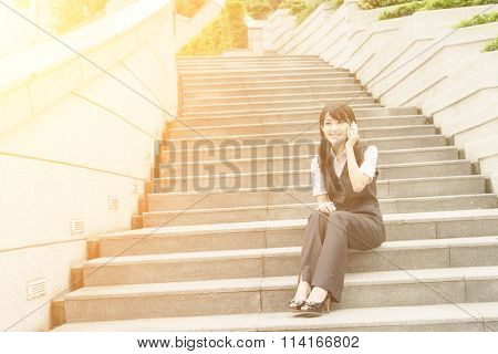 Asian business woman sit on stair and talk on cellphone in daytime urban.
