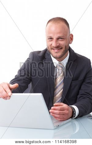 Happy businessman shutting down laptop computer, smiling, looking at camera.