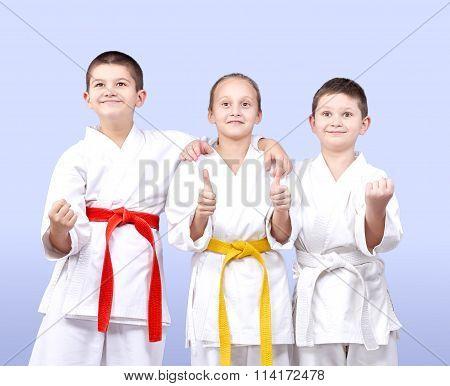 Three sportsmen in karategi stand in rack and show the finger super