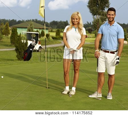 Happy golfers standing on the green, holding golf club, smiling, looking at camera.