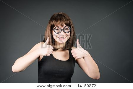 Funny smiling geek girl in glasses with thumbs up. Happy winner nerd woman.