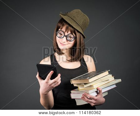 Student in funny glasses with old books in one hand and e-reader in another on grey background. Nerd