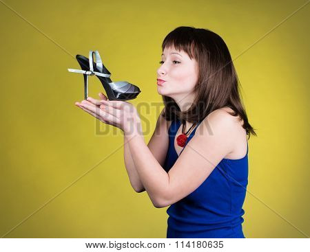 Fashion woman kissing a high-heel shoe. Women love shoes concept. Happy girl and high heels shoes on