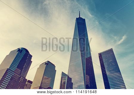 NEW YORK - AUGUST 27: One World Trade Center on the NYC skyline showing the modern design and glass facade in a low angle perspective against a toned cloudy blue sky. August 27, 2015 in New York.