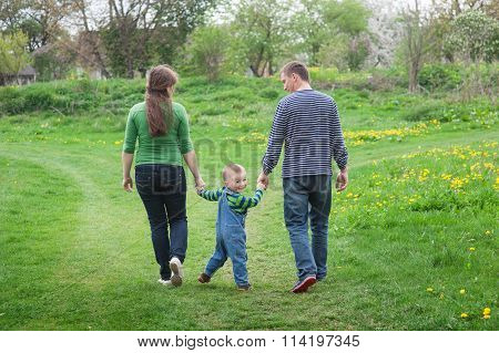 Parents Are Walking With A Little Boy On A Green Spring Meadow On A Footpath