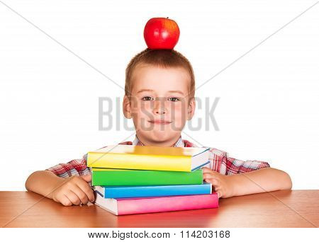 boy with an apple on her head sitting at desk