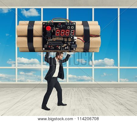 small businessman in formal wear carrying big bomb with timer over light grey background