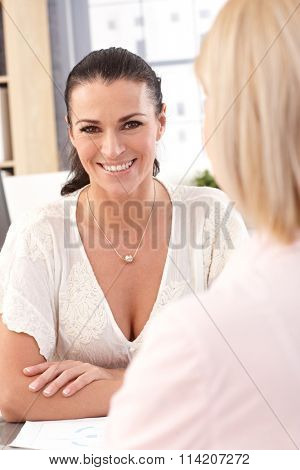 Close up of happy casual brunette businesswoman at office, looking at camera.