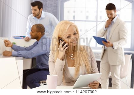 Portrait of busy businesswoman sitting at desk, talking on mobilephone, using tablet computer, smiling.