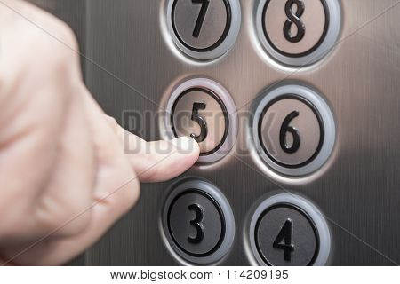 Forefinger pressing the fifth floor button in the elevator