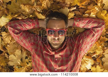 Guy lying on the ground and enjoying fall season