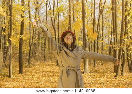 Woman throwing yellow leaves