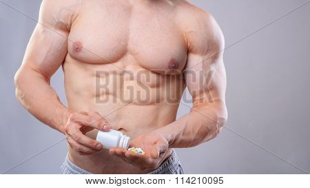Bodybuilder with white jar and pills on neitral grey background in studio