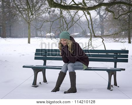 woman sitting alone on park bench in winter