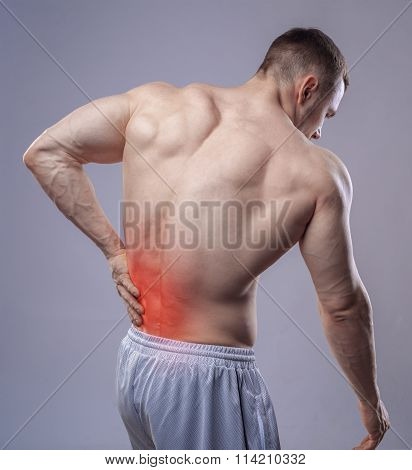 Athlete muscular man has pain in the back. Red spot of backache