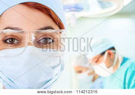 Young female doctor in operation room with her team on background