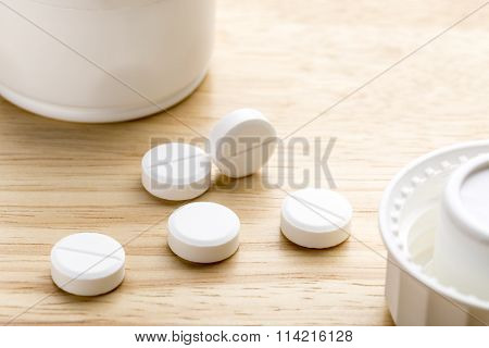 Pills and pill bottle on wooden background