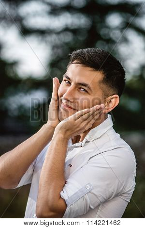 Young Asian man holding his cheeks after shave in park at sunny day