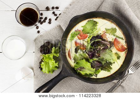 Omelet With Tomatoes And Lettuce In A Black Frying Pan On A Linen Napkin, Coffee And Milk In Glasses
