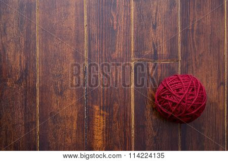 Red Skein Over Wooden Background