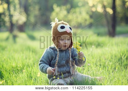 Cute Baby In Knitwears Playing At The Garden
