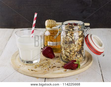 Granola With Nuts In Glass Jar, Strawberry, Honey Jar, Glass Of Milk On White Wooden Table