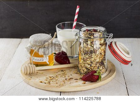 Granola With Nuts In Glass Jar, Strawberry, Glass Of Milk And Jar Of Honey On White Wooden Table