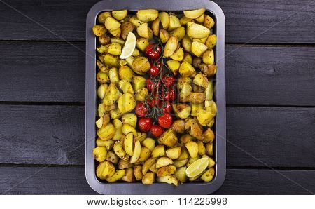 Fried Potato And The Baked Cherry Tomatoes On Branch, Segments A Lime On Baking Sheet On A Wooden Br