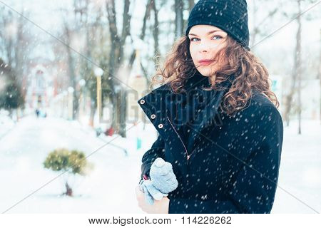 Young Attractive Woman In A Coat On The Street During A Snowfall