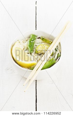 Asian Noodles With Siliculose Haricot, Zucchini And Lemon On White Wooden Background